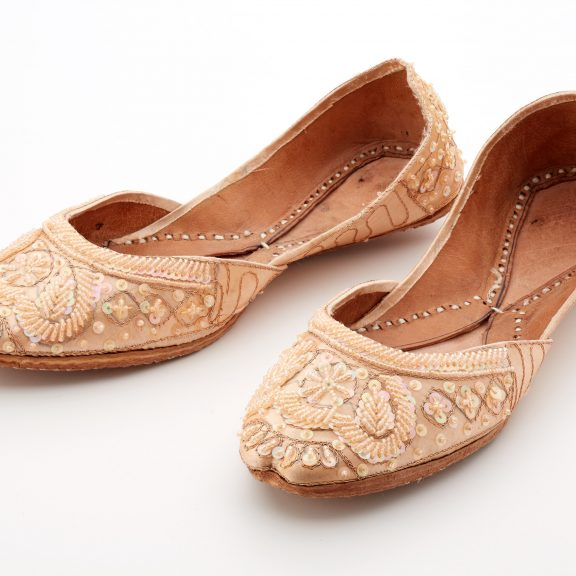 Pale pink shoes with a leather stitched sole. The shoes have a bead, sequin and embroidered stitched decorative pattern decoration.
