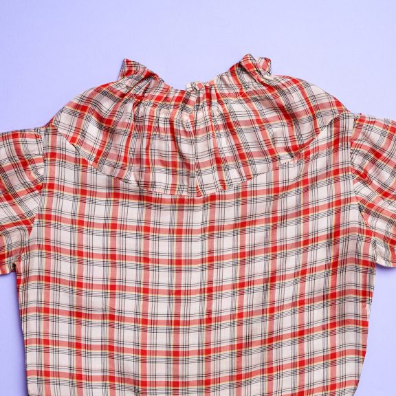 Image shows the bodice and top half of a red, white and black plaid dress with short sleeves and a high neckline with ruffle details.
