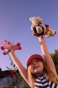 A child gleefully holding up a cuddly toy in each hand. A teddy and a toy pony