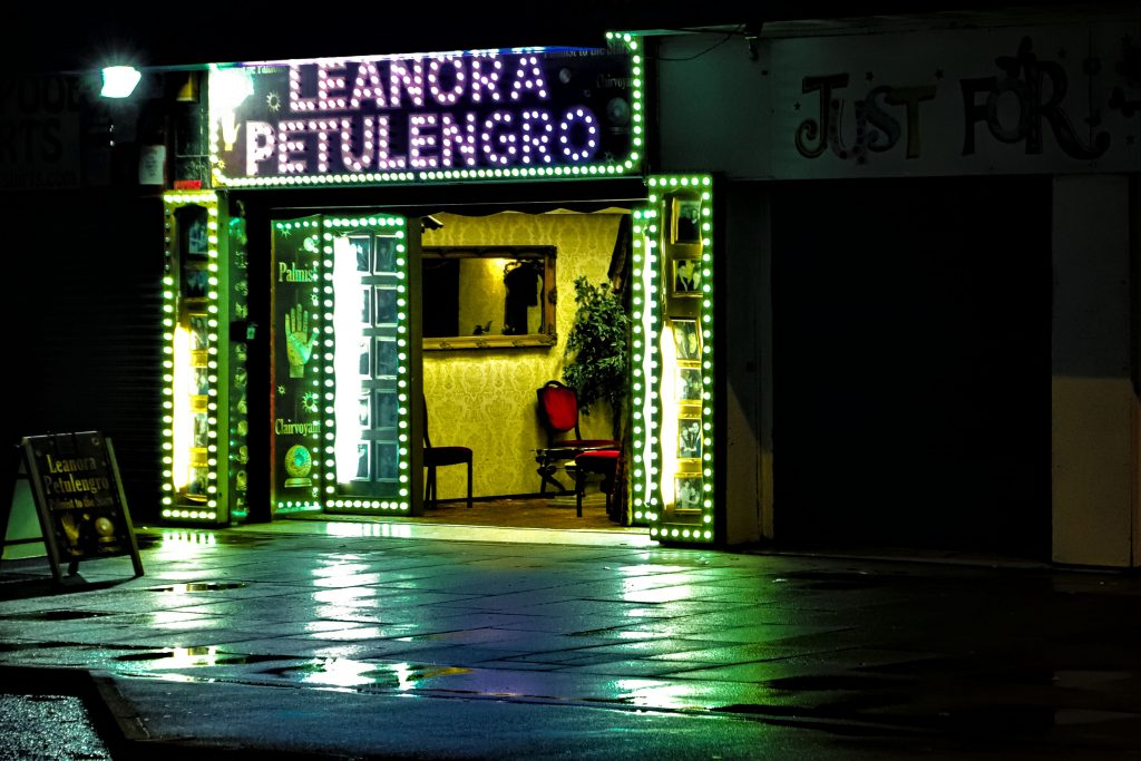 A fairground booth at night all lit up with neon lights