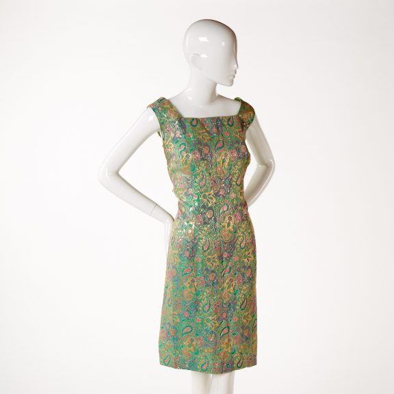 Image shows a mannequin wearing a shift style evening dress woven with stylised green, pink, purple and gold floral motifs.