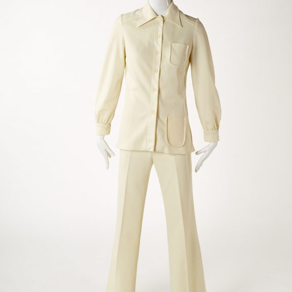 Image shows mannequin wearing a Cream polyester two piece suit. Long sleeve top with single breast, button fastening, 2 pockets on left side. Long length trousers.