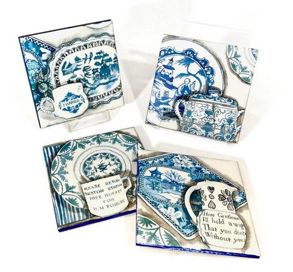 Image shows 4 white ceramic coasters printed with designs of blue and white ceramics including plates, jugs and cups.