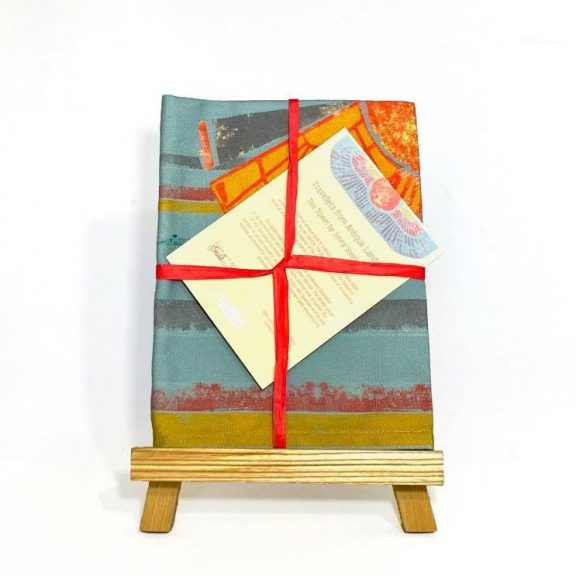 Image shows a rectangular folded patterned tea towel in blues, yellow, orange and brown tones. The tea towel is wrapped in a red ribbon with a card displayed on a small easel.