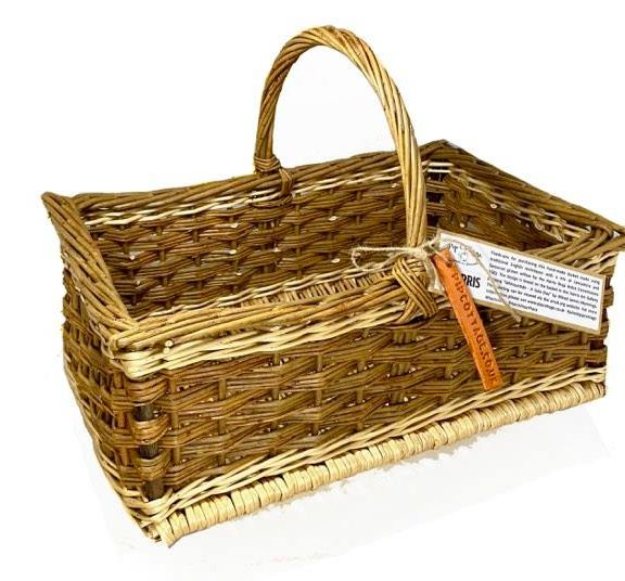 Image shows rectangular woven basket in made from light and dark brown willow. The basket has a large upright curved handle with a tag attatched.
