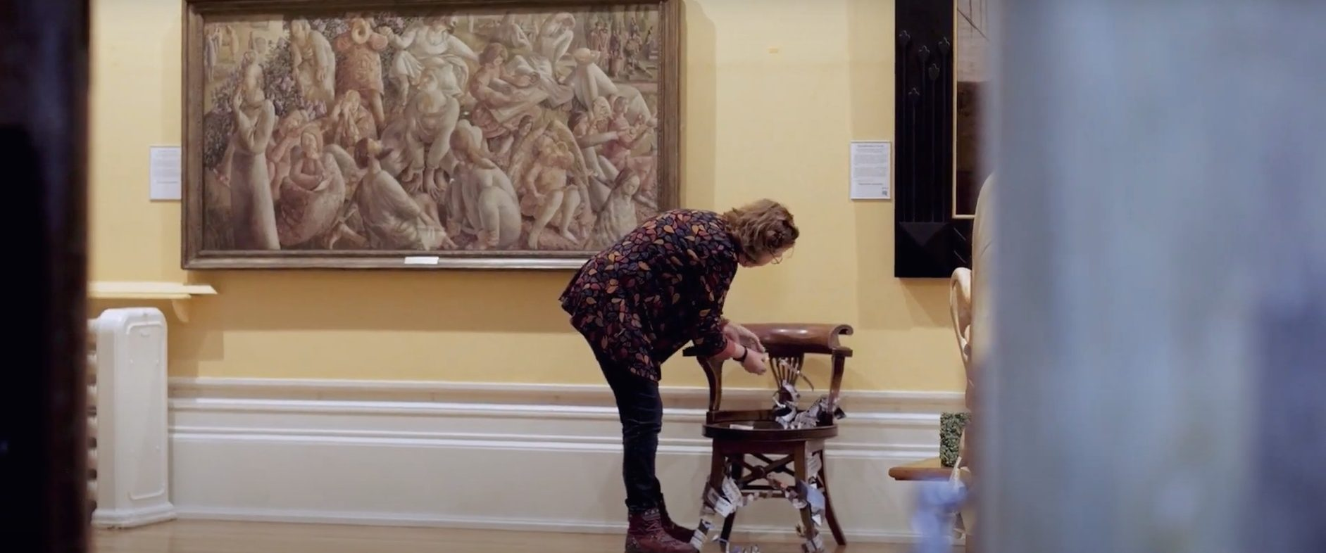 Artist attaching artwork to chair
