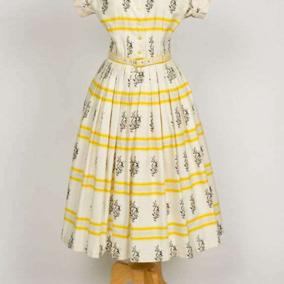 Image shows a yellow and white horizontally striped dress with a long full skirt. The dress has short sleeves, yellow buttons up the front of the bodice and is decorated in a striped pattern with black musical instrument illustrations..