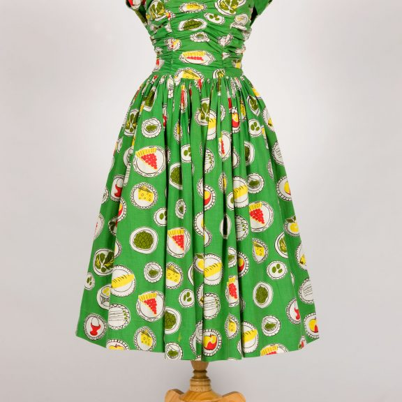 Image shows a green sleeveless dress with a full skirt on a mannequin. The dress is illustrated with colourful illustrations of food including a cheese, pie, boiled egg and fruit.