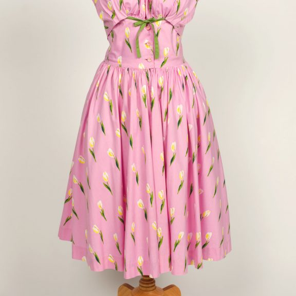 Image shows a pink halter neck dress with a full skirt on a mannequin. The dress is pink with a white and yellow tulip flower pattern with a green tie on the chest.