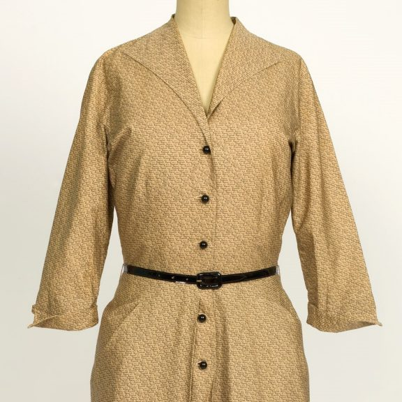 Image shows a light brown shirt style dress on a mannequin. The dress has long sleeves, a black belt at the waist and 5 black buttons down the centre. The dress has a repeat handrwitten text pattern that reads 'Elizabeth Regina 1953'.