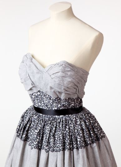 Image shows top half of a dress on a mannequin. The dress is white with a black honeycomb net pattern design and a black floral imitation lace design. The bodice has a black ribbon around the lace and ruched detail on the chest.