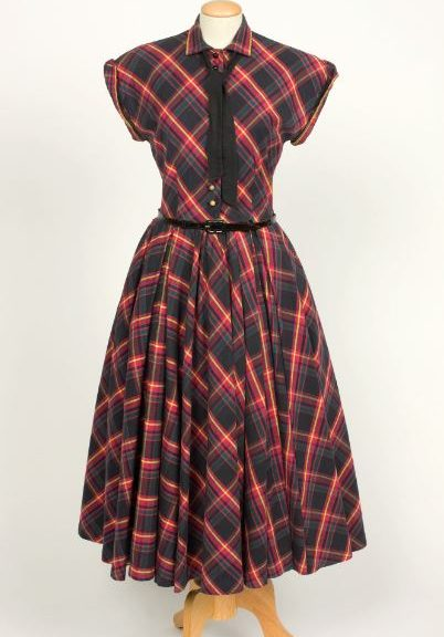 Image shows a tartan shirt style short sleeve dress with a full long skirt. The dress is a red tartan pattern and has a thin black belt at the waist with a back tie around the neck.