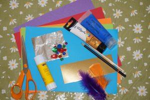 Craft items, coloured card, paint, paint brush, pencil, scissors, glue, and tin foil