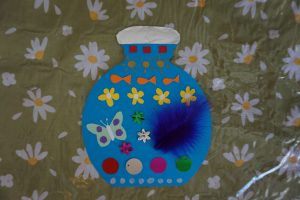 A card bottle decorated with colourful paper, feathers and sequins