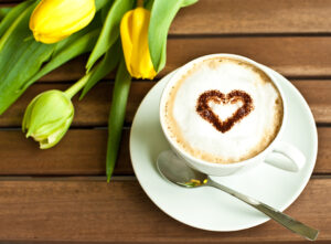 A cup of coffee with a heart and some yellow tulips