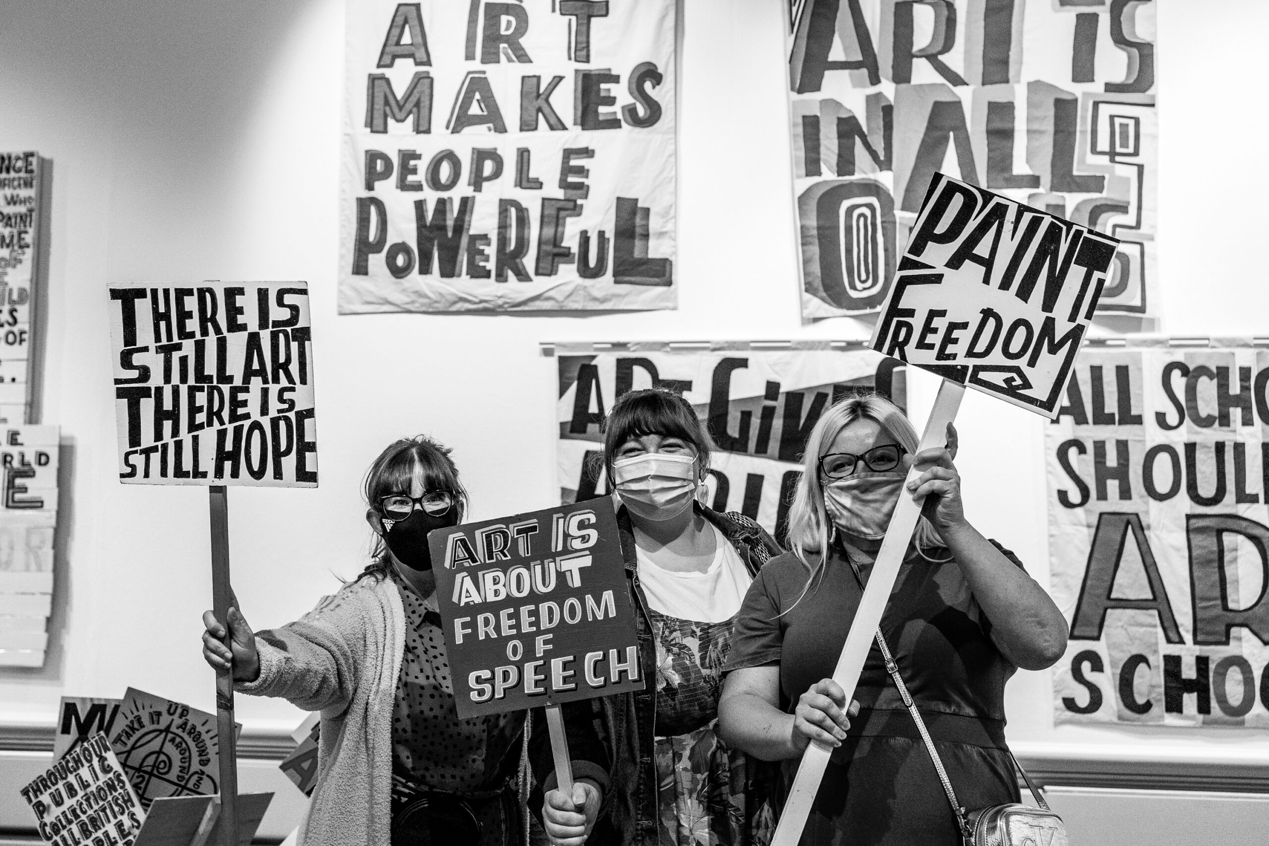 People in the art gallery with placards with messages on from the exhibition