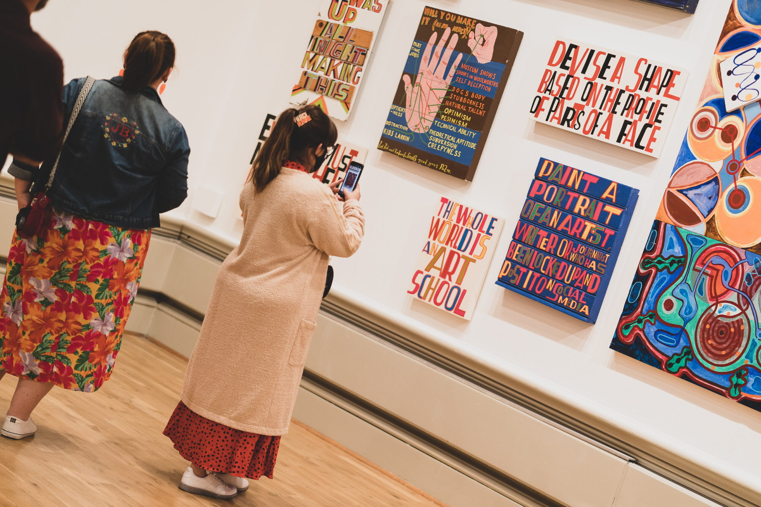 A person looking at colourful art works on a gallery wall