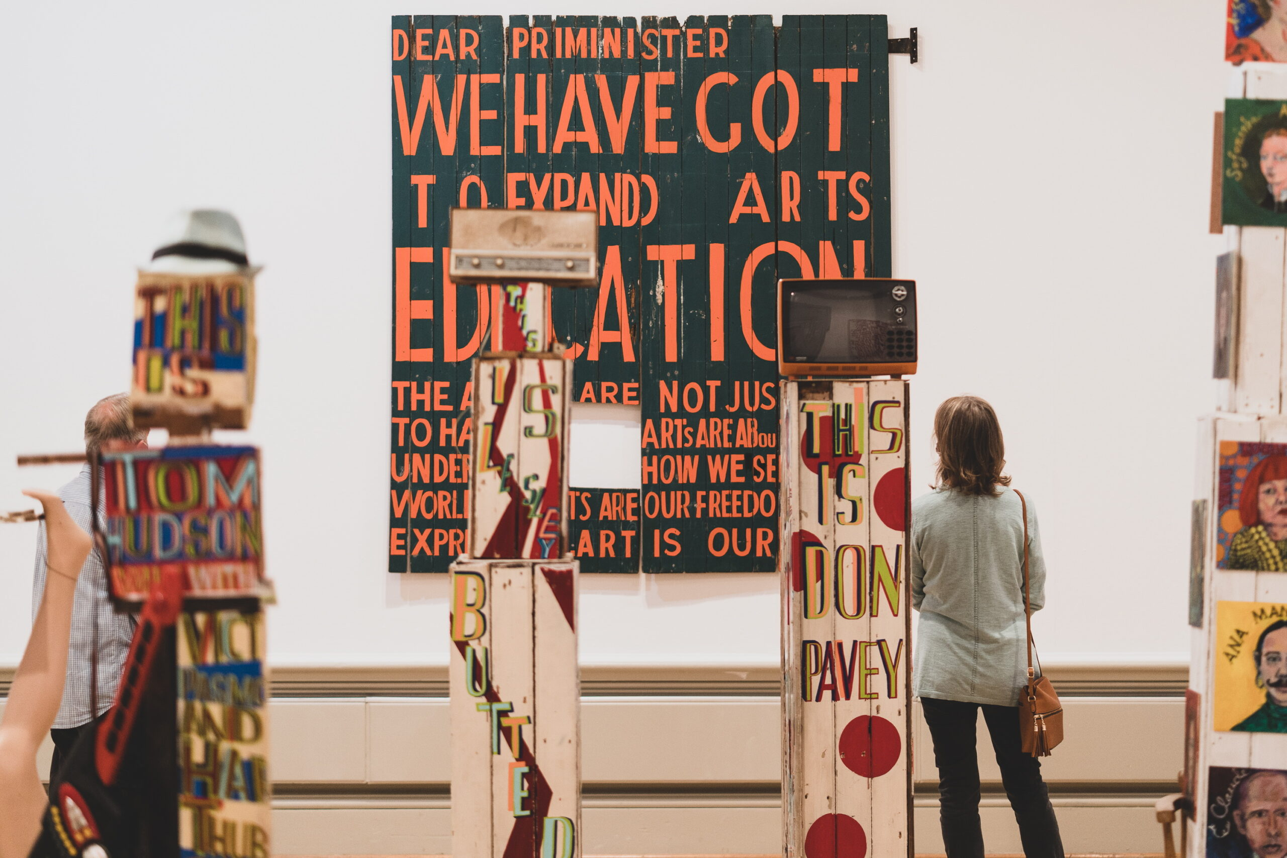 A person looking at the colourful artworks in the Bob and Roberta Smith exhibition
