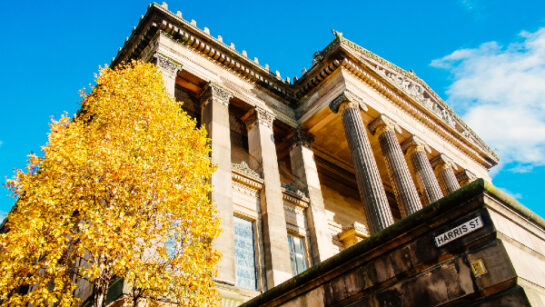 Outside Harris building with autumn tree in foreground.